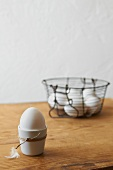 An egg in an egg cup and eggs in a wire basket
