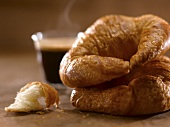 Two Croissants Stacked with a Steaming Espresso in the Background