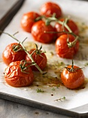 Roasted Cherry Tomatoes on the Vine; Drizzled with Olive Oil, Sea Salt and Thyme Sprigs; On Parchment Lined Baked Sheet