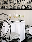 A bistro table laid in black and white with glasses of aperitif