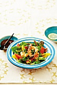 A salad of prawns with citrus fruits, and a bowl of harissa paste
