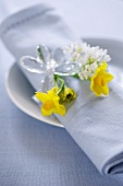A napkin decorated with narcissus on a plate