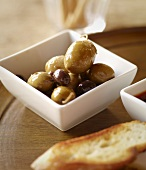 Assorted Green and Black Olives in a Dish with Crostini