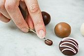 Detail being added to a chocolate bean made from modelling clay using a needle