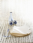 Rice paper on a wooden board, with chopsticks and a sake set to one side