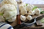 A whole cauliflower and individual florets on a wooden chopping board