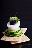 Boiled egg filled with lumpfish caviar and cucumber slices on crispbread