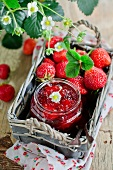 Strawberry jam and fresh strawberries in a basket