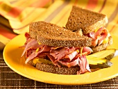 Corned Beef Sandwich with Mustard and Pickles on Pumpernickel Bread; Halved on a Yellow Plate