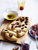 Schiacciata with black olives served with Parma ham