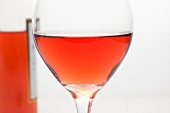 Glass of White Zinfandel Wine with Bottle in Background