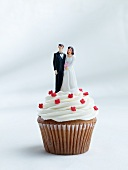 A cupcake topped with a bride and groom