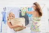 Mutter und Tochter hängen Wäsche auf
