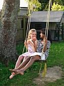 Zwei Mädchen auf einer Schaukel im Garten