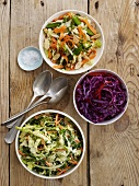 Three Types of Salads in Bowls on a Wooden Table; From Above