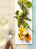 Grilled Stuffed Peppers on a Platter; Glasses of Wine; Forks
