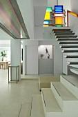 Farbige Leuchtobjekte am oberen Absatz einer modernen Treppe im weissen, offenen Wohnraum