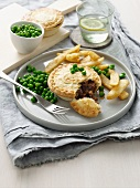 Plate of meat pie, chips and peas