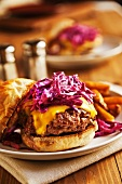 A Cheeseburger topped with red cabbage cole slaw on a plate with french fries