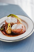 Monk fish wrapped in bacon on a bed of red wine vegetables