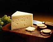 Baby Swiss Cheese Wedge on a Cutting Board with Crackers and Green Grapes