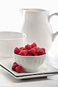 A Bowl of Fresh Raspberries with Bowl and Pitcher