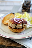 Turkey burger topped with red onions