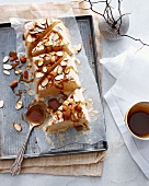 Almond brittle with caramel sauce on a baking tray