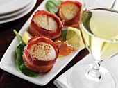 Bacon Wrapped Scallops on a Platter; Glass of White Wine