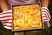 Woman Holding Fresh From the Oven Peach Cobbler