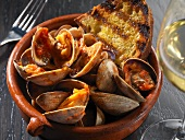 Clams with Grilled Bread in a Bowl; Glass of White Wine