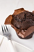 A chocolate muffin in a paper case