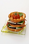A mini club sandwich with aubergines, cheese and ham