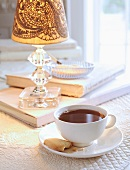 A Cup of Coffee with a Cookie Next to a Lamp and Books