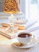 Eine Tasse Tee mit Keks auf Tisch mit Tischleuchte & Büchern