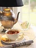 Eine Tasse Tee mit Keks auf Tisch mit teekannenförmiger Lampe