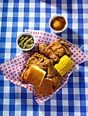 A Basket of Fried Chicken with Corn Bread, Corn on the Cob and Mashed Potato with Gravy