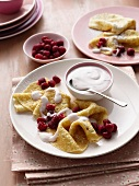 Plate of crepes with fruit and cream