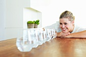 Woman with glasses of water on table
