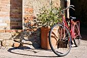 Fahrrad lehnt an einer großen Terrakottavase in der Sonne