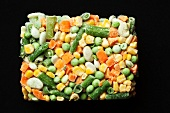 Block of Frozen Mixed Vegetables on a Black Background