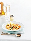 Spaghetti with king prawns and glasses of champagne