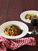 Lamb ragout with rosemary on a bed of pasta with a glass of red wine