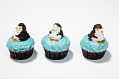 Three cupcakes decorated with penguins on a white surface