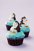 Three cupcakes decorated with penguins on a purple surface