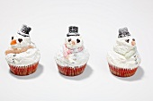 Snowman cupcakes on a white surface