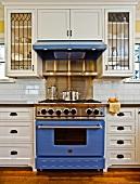 Herd mit blauem Backofen und Dunstabzugshaube in einer Küche mit weissen Schränken