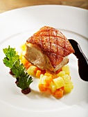 Roast saddle of cochon de lait on a carrot medley served with black pudding puree