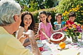Familie sitzt beim Kaffee und Kuchen am Gartentisch