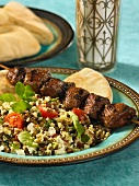 Grilled beef kebab with a couscous and lentil salad